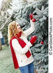 mulher, árvore natal decorando, exterior
