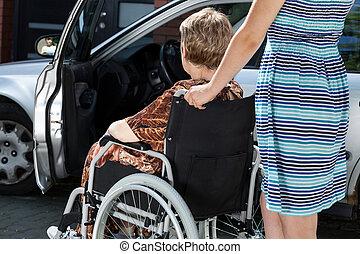 mulher, é, carregar, um, senhora velha, em, um, cadeira rodas