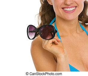 mulher, óculos de sol, jovem, swimsuit, closeup, segurando