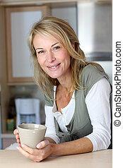 mulher, adulto, assalte, atraente, segurando, cozinha lar