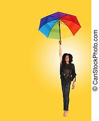 mulher africana, queda, enquanto, prendendo um guarda-chuva
