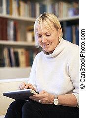 mulher, almofada toque, dispositivo, usando, sênior