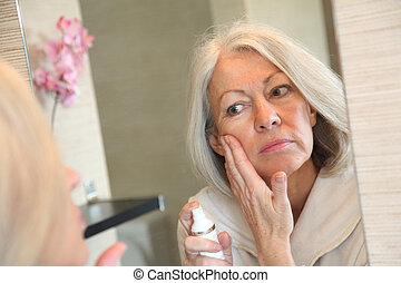 mulher, aplicando, dela, rosto, sênior, moisturizer
