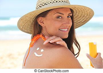 mulher, aplicando suncream, praia