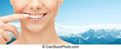 mulher aponta, cima, rosto, dentes, fim, sorrindo
