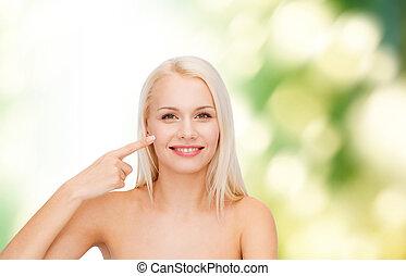 mulher aponta, dela, bochecha, jovem, sorrindo