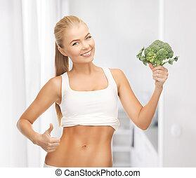 mulher aponta, em, dela, abs, e, segurando, brócolos