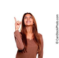 mulher aponta, jovem, cima, olhar, sorrindo