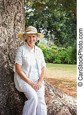 mulher, aposentado, sentando, tronco árvore, sorrindo