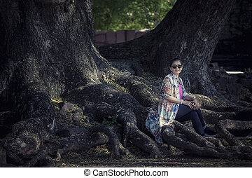 mulher asian, sentando, ligado, grande, chuva, raiz árvore, em, viajando, destino