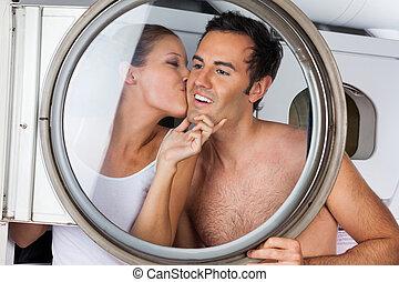 mulher, beijando, homem, ligado, bochecha, em, lavanderia