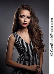 mulher bonita, com, luminoso, maquilagem, e, cabelo longo, batom vermelho, e, longo, cacheados, penteado, posar, em, listrado, vestido, ligado, cinzento, experiência escura