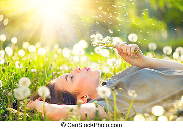 mulher bonita, dandelion, jovem, campo, soprando, grama verde, mentindo