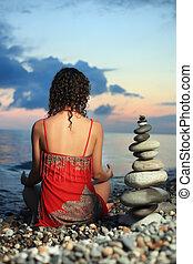 mulher bonita, em, vermelho, sundress, meditar, perto, para, piramide, de, seixo, ligado, pedra, seacoast, em, noite, sentando, por, costas