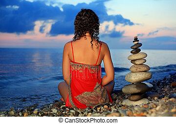 mulher bonita, em, vermelho, sundress, sentando, perto, para, piramide, de, seixo, ligado, pedra, seacoast, em, noite, sentando, por, costas