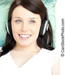 mulher bonita, escutar, música, mentindo, ligado, um, sofá