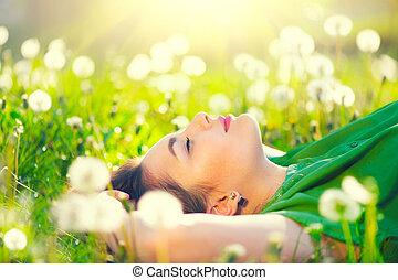 mulher bonita, jovem, campo, dandelions, grama verde, mentindo