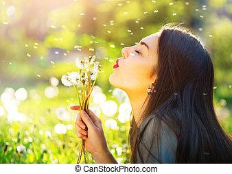 mulher bonita, jovem, dandelions, soprando, sorrindo