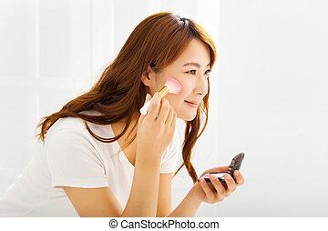 mulher bonita, jovem, escova maquiagem