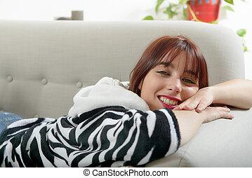 mulher bonita, jovem, mentindo, sofá
