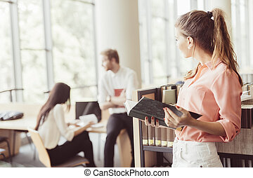 mulher bonita, lendo um livro, em, um, biblioteca