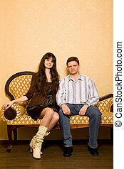 mulher bonita, sala, sentando, sofá, homem jovem