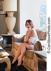 mulher bonita, sala, sentando, sofá, jovem, luxo, sorrindo