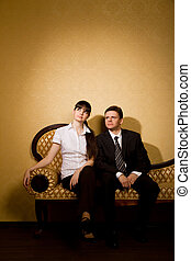 mulher bonita, sala, sentando, sofá, jovem, paleto, homem negócios
