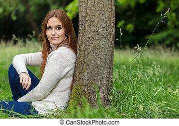 mulher bonita, sentando, árvore, jovem, contra, inclinar-se