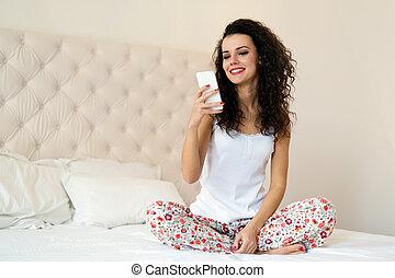 mulher bonita, sentando, cama, telefone, enquanto, usando