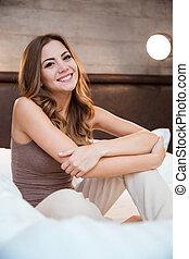 mulher bonita, sentando, jovem, cama, sorrindo