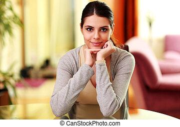 mulher bonita, sentando, jovem, tabela, lar, sorrindo