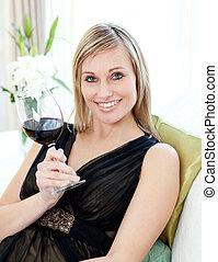 mulher bonita, sentando, sofá, drining, vinho tinto