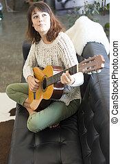 mulher bonita, sentando, sofá, jovem, violão jogando