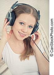 mulher bonita, sofá, fones, jovem, enquanto, escutar música, desfruta, mentindo