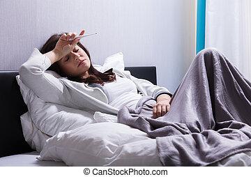 mulher, cama doente, segurando, termômetro, mentindo