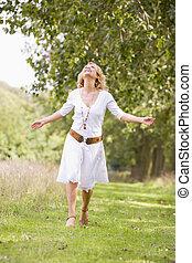 mulher caminhando, ligado, caminho, sorrindo