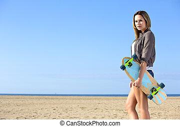 mulher caminhando, ligado, um, praia, com, um, skateboard