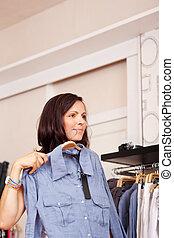 mulher, camisa, afastado, olhar, enquanto, tentando, loja roupa