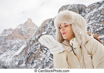 mulher, casaco pele, neve, mão, soprando, ao ar livre, chapéu branco