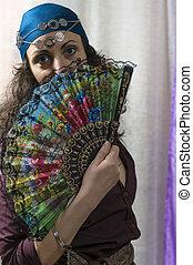 mulher, colorido, dela, jovem, rosto, atrás de, ventilador, escondendo