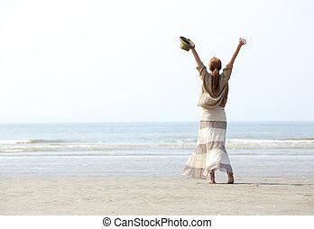 mulher, com, braços levantados, praia