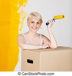 mulher, com, caixa papelão, e, pintar rolo
