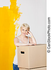 mulher, com, caixas cartão, contra, metade, amarela, parede pintada