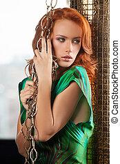 mulher, com, chain., bonito, jovem, cabelo vermelho, mulher segura, correntes, e, olhando