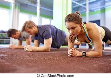 mulher, com, coração-taxa, tracker, exercitar, em, ginásio