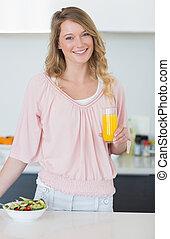 mulher, com, salada, segurando, suco laranja, em, cozinha
