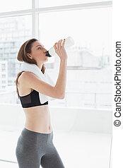 mulher, com, toalha, ao redor pescoço, água potável, em, condicão física, estúdio