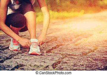 mulher, corredor, jovem, cadarços sapato amarrando