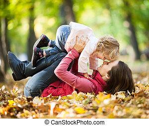 mulher criança, tendo divertimento, em, outono, parque